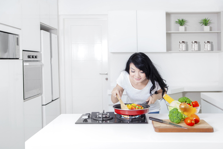 Picture of a pretty Asian woman cooking in the kitchen and sniff meal on the frying pan, shot at home 版權商用圖片 - 65711126
