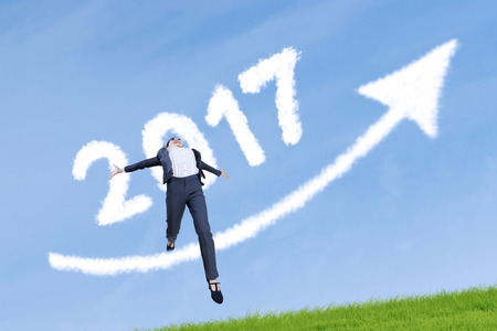 year increase: Beautiful businesswoman celebrating her success while jumping on the meadow with clouds shaped numbers 2017 and upward arrow