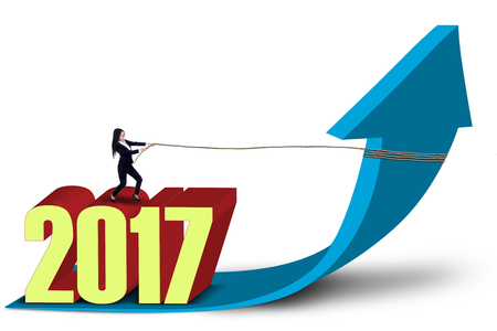 pulling beautiful: Beautiful entrepreneur pulling a blue arrow upward with rope while standing above numbers 2017