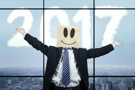 pasteboard: Image of male entrepreneur wearing cardboard on his head while raising hands for celebrating his success with cloud shaped number 2017 in the sky Stock Photo