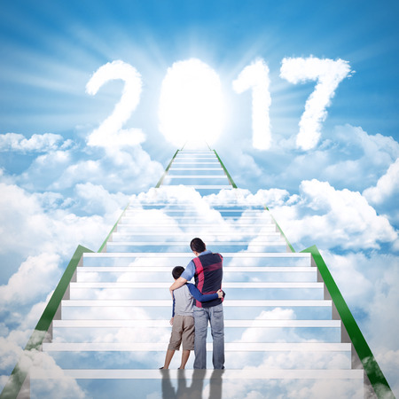 son of god: Image of father hugging his son and standing on the stair while looking at cloud shaped number 2017 in the sky