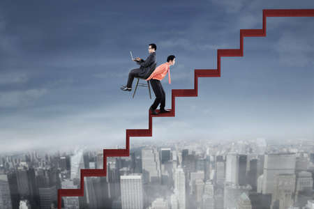 upward struggle: Image of businessman going up the stair while carrying chair with his colleague using laptop and sitting on the chair
