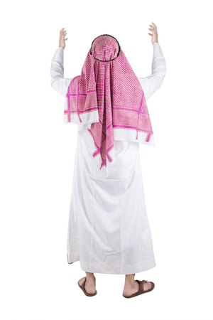 Back view of muslim man standing and praying in the studio while raising his hands, isolated on white background