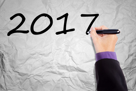 hand pen: Hand of business is holding a pen while writing numbers 2017 on the crumpled paper