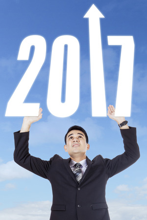 upward struggle: Portrait of male entrepreneur lifting up number 2017 with upward arrow