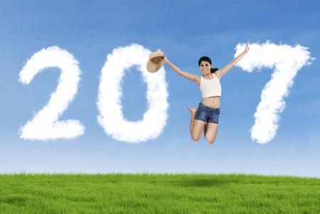 simbolo de la mujer: Hermosa mujer saltando y sonriendo a la cámara mientras que forman el número 2017, por el campo