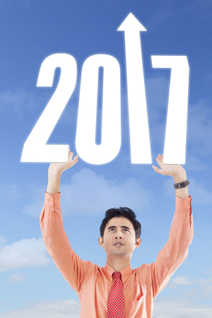upward struggle: Portrait of male entrepreneur with number 2017 and upward arrow in the clear sky