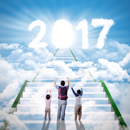 raising: Portrait of a happy family is raising hands while looking at cloud shaped number 2017 on cloudscape Stock Photo