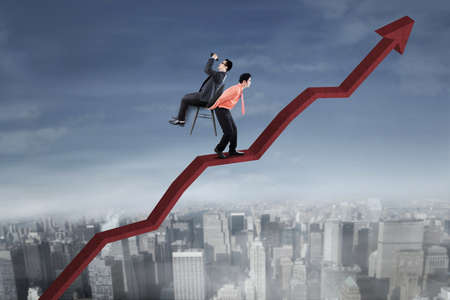 upward struggle: Image of a strong male entrepreneur walking on the upward arrow while carrying his colleague sitting on the chair and using binoculars Stock Photo