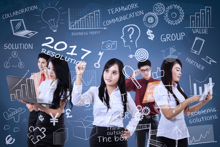 group strategy: Group of busy business team working together to making business strategy with leader writes business resolution for 2017