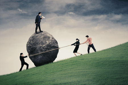 Image of male business leader with megaphone commanding his team for pulling big stone with rope on the hill