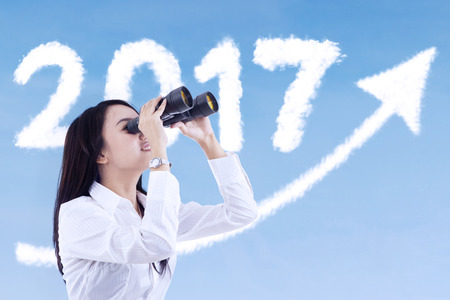 Image of female entrepreneur using binocular while looking cloud shaped number 2017 and upward arrow on the blue sky