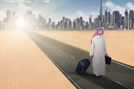 briefcase: Picture of arabian man walking on the highway while carrying a suitcase and a briefcase