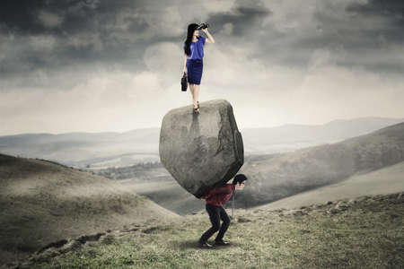 overloaded: Portrait of woman entrepreneur standing on the stone and looking through binocular while her partner lifting boulder on the hill Stock Photo