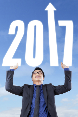 upward struggle: Businessman raises hands with number 2017 to the sky, concept of increased business in the future