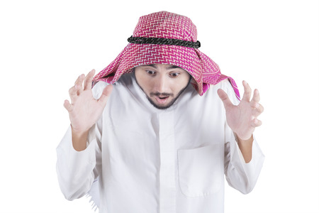 hombre arabe: Portrait of shocked arabian man wearing islamic clothes, shot in the studio isolated on white background