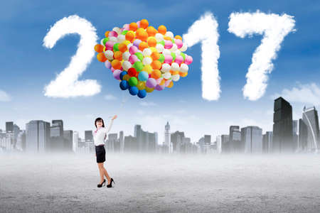 high spirits: Female entrepreneur standing and holding balloons with clouds shaped number 2017 on the sky Stock Photo