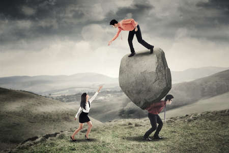 business in hand: Image of young businessman helping his colleague by hand while standing above the stone with his partner on the hill