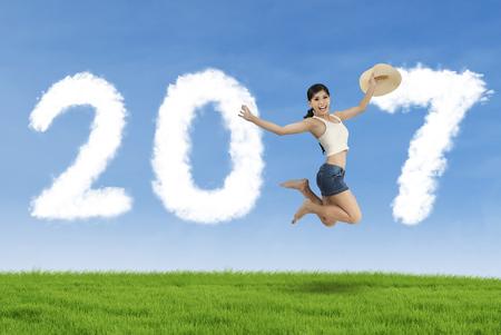 personas saltando: Imagen de la mujer joven con el sombrero y el baile en el prado mientras se forman los números de 2017 con la nube Foto de archivo