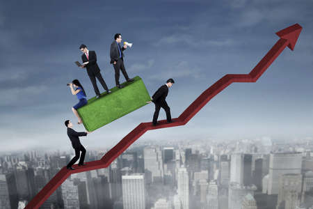 upward struggle: Busy business people above a boulder with their partners bringing a boulder while walking on the chart upward