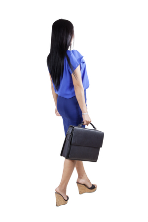briefcase: Rear view of young woman walking in the studio while carrying a briefcase, isolated on white background Stock Photo