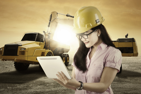 computer engineer: Image of young female engineer using a tablet computer with an excavator and truck in the background
