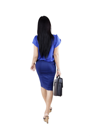 people walking white background: Back view of a female entrepreneur walking in the studio while carrying a briefcase, isolated on white background