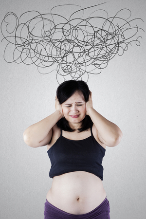hispanic woman: Portrait of a pregnant woman is having headache with tangled arrows on the wall