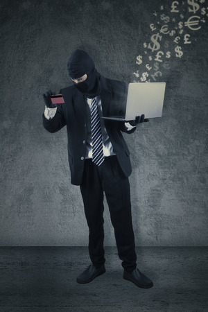 Male thief wearing a mask and holding a credit card with a laptop computer. Concept of hacker stealing a credit card information Stock Photo