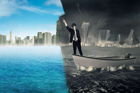 rise: Businessman standing on a boat while using a roller to change a collapse city into a new city. Concept of an effort or change to success