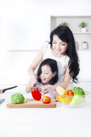 teaches: Young mother teaches her child making salad with vegetable in the kitchen
