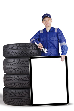 advertise: Image of young male technician is holding wrench and empty whiteboard while leaning with a pile of tyres Stock Photo