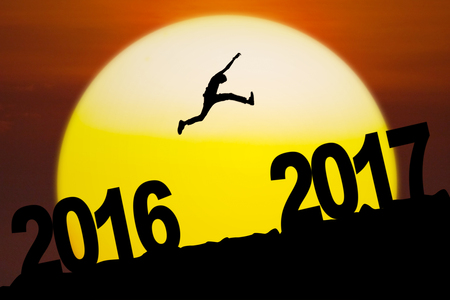 Silhouette of a young man jumping from numbers 2016 to numbers 2017 in the sunrise