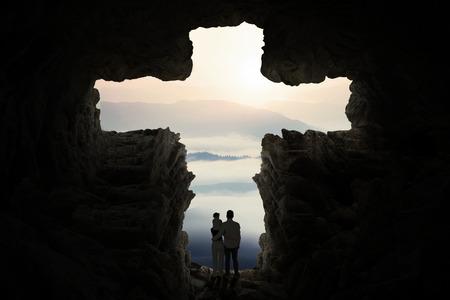 sacra famiglia: Silhouette di due genitori e loro figlia che si trovano all'interno di una croce a forma di grotta guardando fuori
