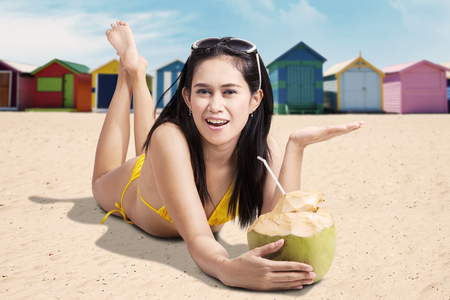 brighton: Pretty woman with swimsuit holding a coconut drink while lying near the beach hut