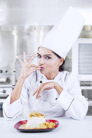 Portrait of young chef showing ok sign for perfection with delicious food on the plate while Stock Photo