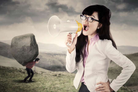 commanding: Businesswoman using a megaphone for commanding her employee to carry a  big stone on the hill