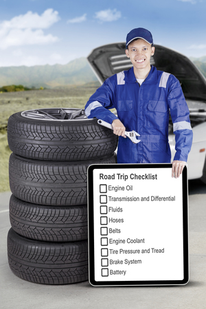 Image of mechanic showing a road trip tips on the board and holding a wrench while standing close a pile of tires