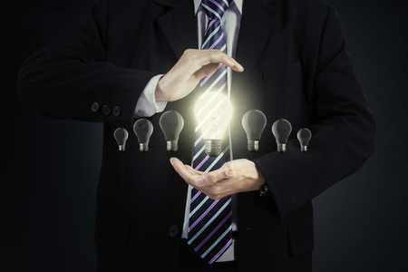 hand hold: Businessman chooses one bright lamp on his hands, concept of new innovation Stock Photo