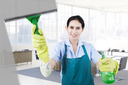 housemaid: Happy housemaid cleans the dirty mirror by using glass cleaner at the office Stock Photo
