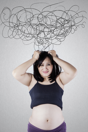 Image of stressful pregnant woman holding her hair with tangled arrows on the wall