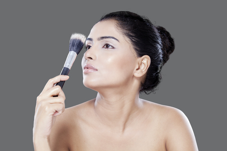 mujer maquillandose: Beautiful young model with clean skin holding makeup brushes, shot in studio on gray background