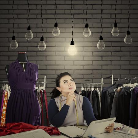 Beeld van manierontwerper die gloeilamp bekijken terwijl het houden van een digitale tablet in haar werkplaats