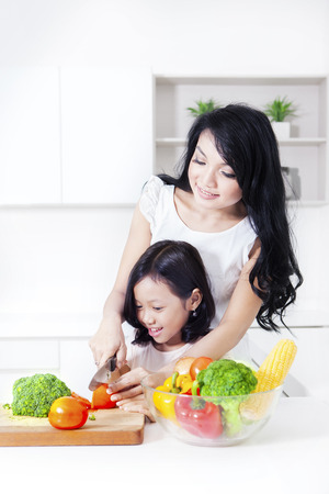 Cute girl cutting a tomato helped by mother while standing in the kitchen