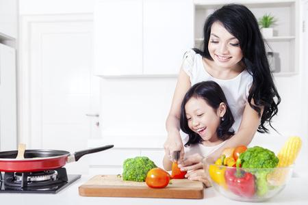 mama e hija: Hermosa madre enseña a su linda chica a cocinar utilizando un cuchillo en la cocina