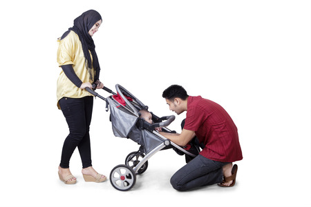 perambulator: Picture of young parents playing and strolling with their baby on the stroller, isolated on white background