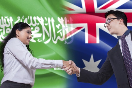 Photo of a young Australian businessman shaking hands with Arabian businesswoman in front of Australian and Arabian flags
