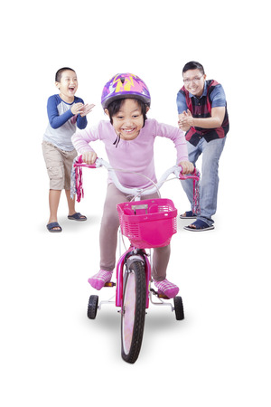 kids playing: Portrait of little girl wearing helmet and pedaling bicycle with her family in the studio