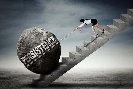 trabajando duro: Empresaria asiática joven que tira una piedra grande con el texto persistencia mientras que sube por una escalera