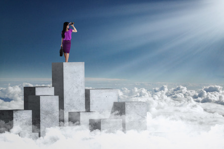 using binoculars: Image of a young businesswoman standing on the concrete wall and looking at blue sky using binoculars